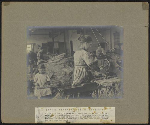 Meisjes in de Dutch Straw Works Company (de strohulzenfabriek) te Helmond. Het ene meisje haalt de stromatjes uit de naaimachine, de andere buigt de matjes tot huls en bevestigt de uiteinden door middel van een touwtje. De productie ligt op gemiddeld 3000 stuks per dag