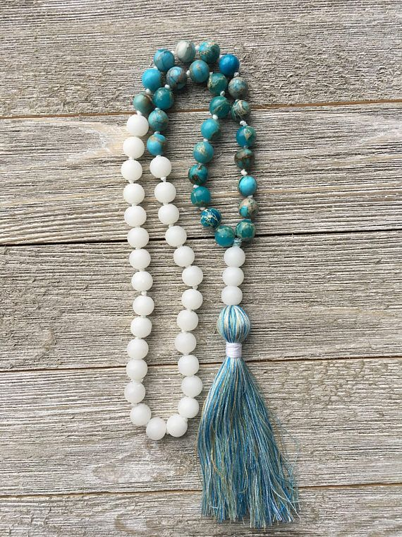 A hand-knotted 54 beads mala. I used imperial jasper and white matte glass beads. I used 3 glass white beads as guru beads and I made a tassel using multiples tone of blues, white and beige. Chakra: All Imperial Jasper properties: Jasper is known as the supreme nurturer. It supports the