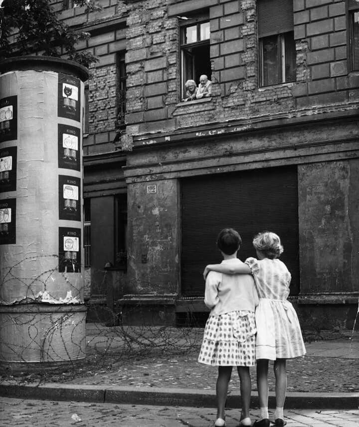 #foto che hanno segnato un'epoca Due ragazze tedesche della zona occidentale, parlano con i nonni che si trovano in quella orientale, separati da una barricata di filo spinato, 1961