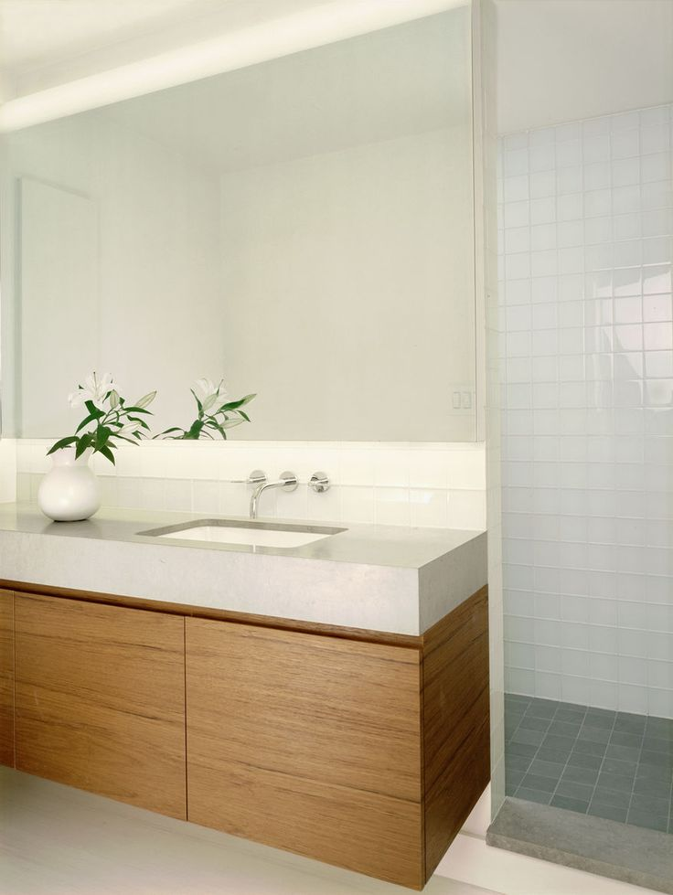 """What looks like a powder room has a shower for guests tucked behind its rear wall. The top 4"""" of silver were sandblasted off the back of the vanity mirror to diffuse a concealed LED light."""