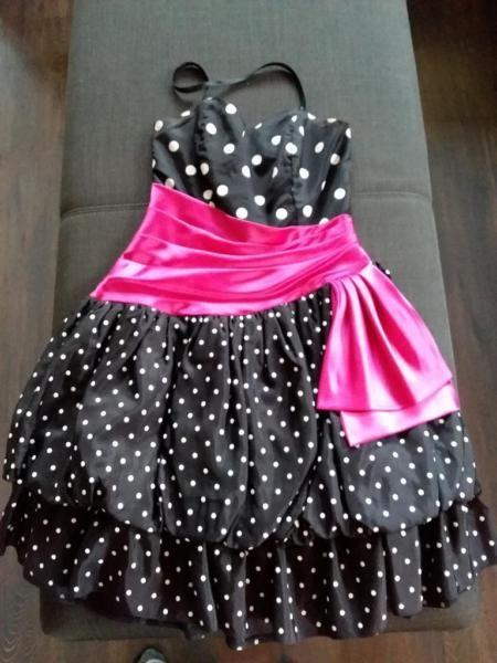 Ein süßes Kleid schwarz mit weißen Punkten im Stil der 50er und 60er Jahre, wenn man einen Petticoat darunter trägt. (es ist kein Pettycoat dabei). Das Kleid wurde nur ein paar Mal getragen.Die Taille wird durch eine rosa Schärpe gut betont.Sehr sexy und luftig für Fasching oder den kommendenSommer.Länge ca. 80 cm Größe 38Wir sind ein Nichtraucherhaushalt.