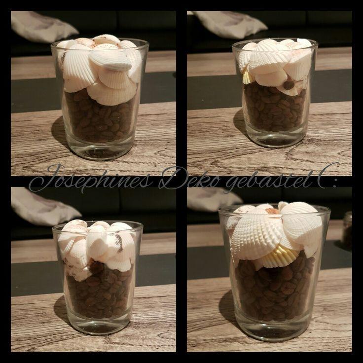 Glas gefüllt mit Kaffebohnen und darauf Muscheln