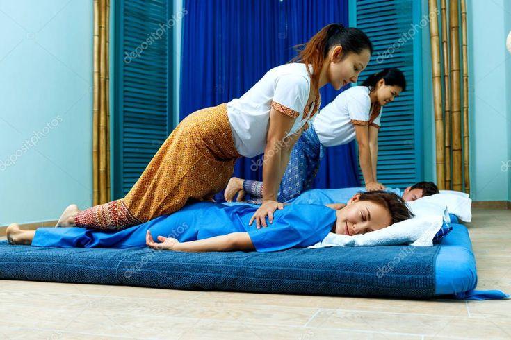 Two thai masseuses synchronously doing thai massage