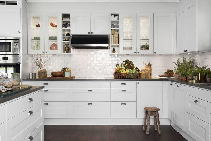 Et klassisk kjøkken med fronten Studio, her i lysegrått. Døren på bildet har et slett speil med ramme, og kan fås i hele 15 farger samt i flere ulike utførelser i tre. Tradisjonelt vitrineskap i kombinasjon med passende benkeplater, åpne hyller og vindu med sprosser gjør dette til et moderne kjøkken uten å miste sjarmen på veien | Drømmekjøkkenet