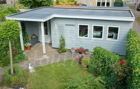 Houten garage met plat dak, blauw geschilderd en luifel