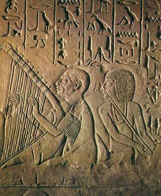 """Detail - Blind harpist playing with """"orchestra"""" for the tomb owner Patenemheb. Tomb of Patenemheb. XVIII Dynasty, 1570-1293 BC, New Kingdom. Relief, limestone, detail. Necropolis at Saqqara. Rijksmuseum, Leiden, The Netherlands. Source: H. Hickmann, Music History in Picture. Egypt. Vol. II. VEB German Publishing House, Leipzig, 1961."""