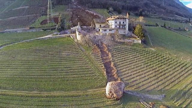 Capricious Mother Nature destroyed a building with a giant boulder in northern Italy, with an even bigger boulder missing a three-story farm house by a just few inches, stopping right at its main entrance.