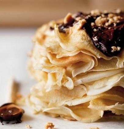 Lacey crepes dressed with thick, warm chocolate and crumbled fudge