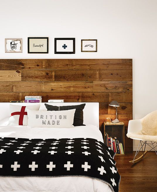 Located in the bungalow, the master bedroom was updated. On the CB2 Alpine bed are Anichini linens and a Pia Wallén Crux Blanket; Suttles and her mother made the throw pillows. The headboard was crafted from the house's original wood. The couple repurposed old fruit crates as bedside tables and hung the Hugo Guinness prints.