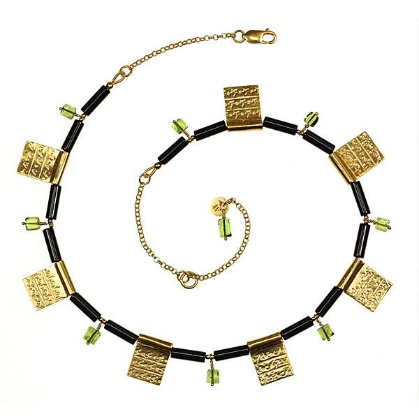 24ct gold plated on silver, onyx and peridot by Sima Vaziry jewellery. The seven gold plates on this beautiful, eye catching necklace, are inscribed with the names of the seven stopping locations for a pilgrim on Hajj: Mikat, Mecca, Mina, the Plain of Arafat, Muzdalifa, the Plain of Mina, and Mecca again. The calligraphy is derived from samples handwritten in Arabic by the designer herself.