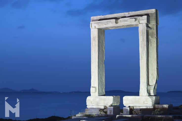 "Portara, Temple of Apollo on Naxos Considered the main landmark and symbol of Naxos, situated in the tiny island of Palatia in the harbour of Naxos, lies the single remaining part of the incomplete temple of Apollo of 530 B.C. Constructed during the tyranny of Lygdamis, ""Portara"" is a huge marble gate, which consists of four marble parts weighing about 20 tons each. Portara today is connected with the Naxos mainland through a paved pathway. #Mentor #HistoricRoutes #MentorInGreece"