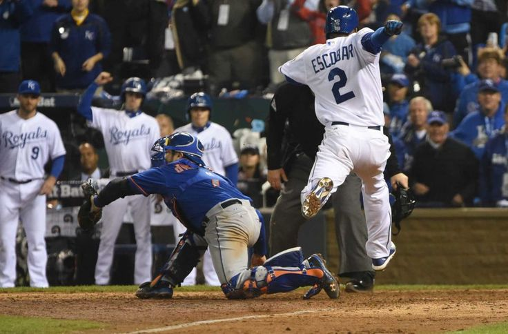 New York Mets catcher Travis d'Arnaud (7) is late with the tag as Kansas City Royals shortstop Alcides Escobar (2) scores winning run in the fourteenth inning during Game 1 of the World Series against the Kansas City Royals at Kauffman Stadium on Tuesday, Oct. 27, 2015.