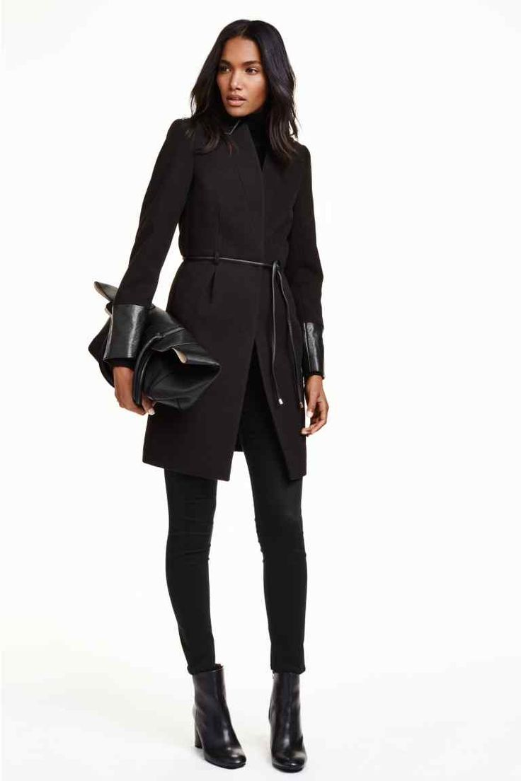 Přiléhavý kabát: Přiléhavý kabát z plstěné látky s koženkovými detaily a skrytými druky. Má kapsy vložené do bočních švů a úzkou vázačku v pase. S podšívkou.