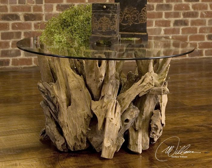 Unfinished teak driftwood is sculpted into a beautiful rustic table base and capped with a round clear glass tabletop. This beautiful, all natural table will be a favorite conversation piece. No two a