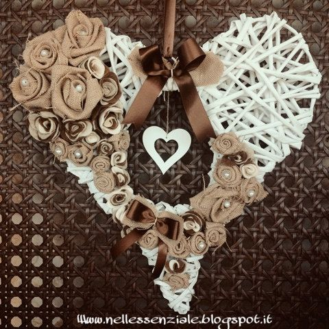 Ghirlanda a forma di cuore con foro centrale nel quale trova alloggio un cuore in legno. La ghirlanda è realizzata in carta intrecciata con