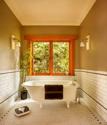 "The master-bath ""tub room"" includes a restored 1931 Stanley clawfoot bathtub. Walls are an earthy taupe."