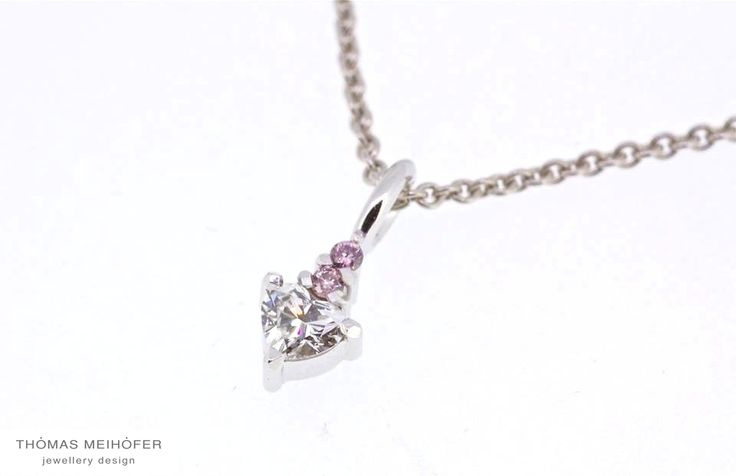 Sometimes the best things come in tiny packages!  White heart shaped diamond accentuated with two tiny pink round brilliant cut diamonds delicately set into white gold claws. Each claw has been facetted to a mirror finish. Perfect for those women who want the most delicate glimmer of light at their throat…