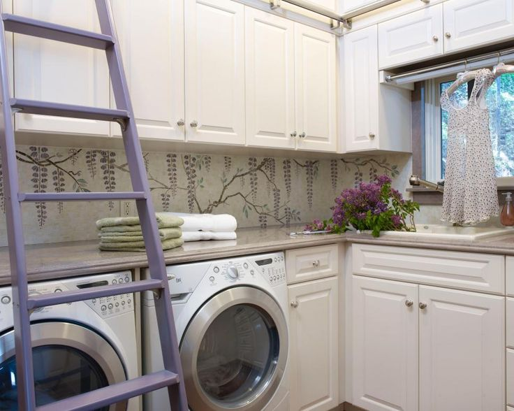 Custom white cabinetry gives this charming laundry room a fresh look. A library-style ladder provides access to additional storage space while adding a pretty pop of color to the room.