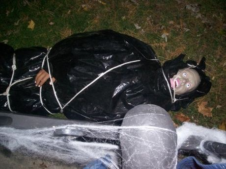 A fake dead guy...easy!! Just need a rubber mask and hand, rope, a black contractor trash bag (body bag!), something to stuff it with.... and voila!
