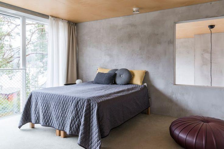 Minimalistisk møblert soverom med betongvegg