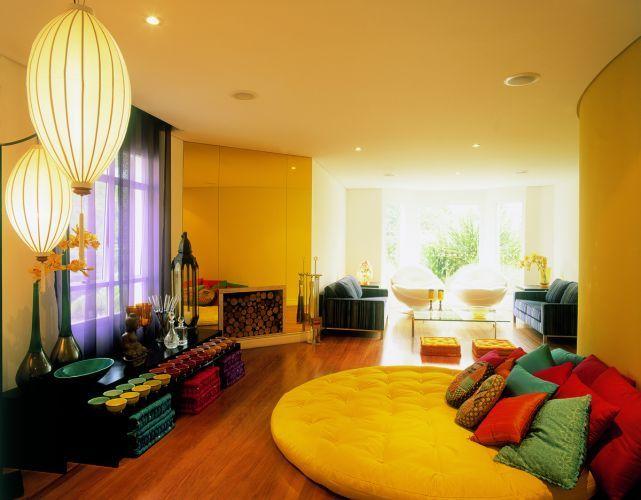 Na sala de lareira, Brunete Fraccaroli usou um futon gigante recoberto por almofadas confortáveis. A paleta de cores e as luminárias revelam a inspiração oriental do ambiente