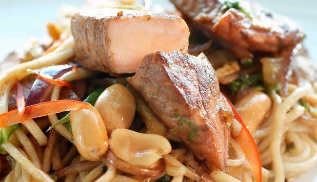 Laks passer godt i en wokpanne sammen med gode grønnsaker. Peanøttene gir denne woken en spennende vri.