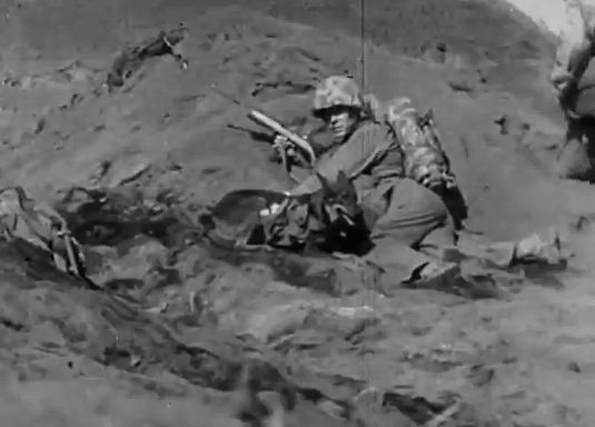 US Marine with his war dog under fire during the Battle of Iwo Jima, 1945. -