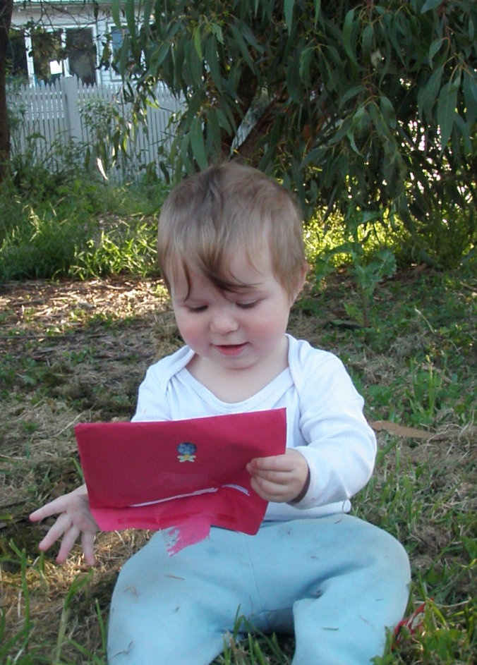 Baby opening red envelope and wondering what's inside - a first Love Santa letter!