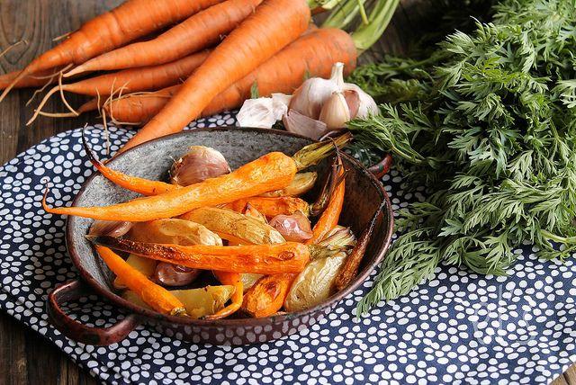 Recette de Pommes de terre et carottes rôties au four - Ingrédients : 1 petite botte de carottes fanes, 600 g de pommes de terre nouvelles, 2 têtes d'ail...