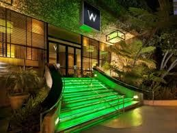 this hotel uses its planted wildlife to compliment its entrance, and then uses green lighting to blend both hotel and plant life together