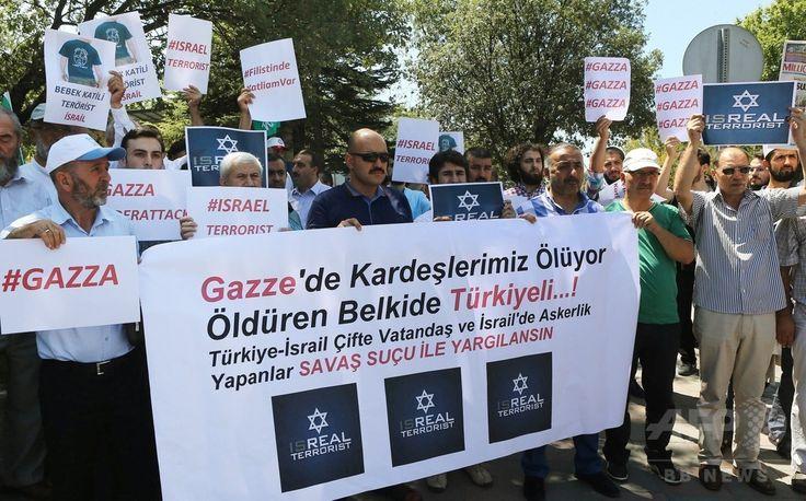 トルコ首都アンカラ(Ankara)の国会前で、イスラエル軍によるパレスチナ自治区ガザ地区(Gaza Strip)攻撃の中止を求め、プラカードなどを掲げるトルコ人。垂れ幕には「ガザにいるわれわれの兄弟は殺されている。殺人者はトルコ出身かもしれない。トルコ・イスラエルの二重国籍者、イスラエル軍に従軍したものは戦争犯罪で裁かれるべきだ」と書かれている(2014年7月31日撮影)。(c)AFP/ADEM ALTAN ▼2Aug2014AFP|「イスラエル軍は攻撃を中止せよ」、世界各地で反戦デモ http://www.afpbb.com/articles/-/3022045 #Ankara #against_Israel