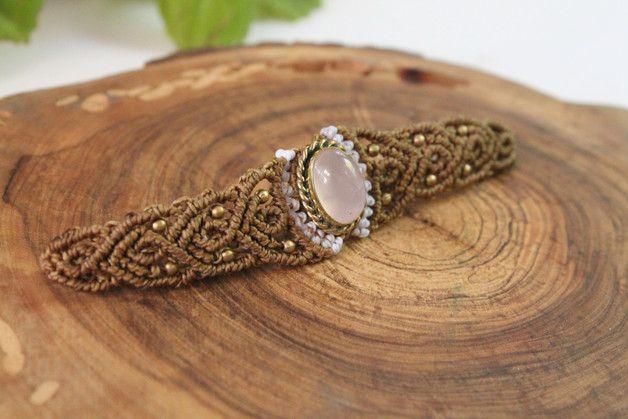 Pulsera brazalete en macramé hecho totalmente a mano con una piedra de cuarzo rosa engarzada en bronce y pequeñas cuentas, el cierre es con un nudo corredizo ajustable a la muñeca. Solo 1 unidad...