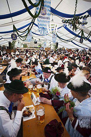 La gente en traje de Baviera dentro de la tienda de cerveza, Oktoberfest, Munich…