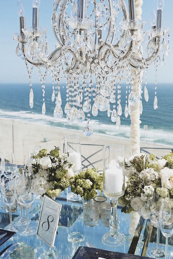 Sparkling crystal chandeliers were suspended above rectangular glass tables topped with mercury-glass votive candle holders, pillar candles, and short arrangements of ivory and light green flora. #Tablescape #BeachWedding Photography: Daniel Kincaid Photography. Read More: http://www.insideweddings.com/weddings/brittney-palmer-and-aaron-zalewski/595/