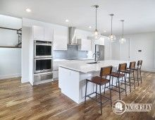 White Kitchen with custom cabinets, glass backsplash, extra long island, wood accents. Custom Infill in Crestwood, Edmonton by Kimberley Homes  #interiordesign #newhomedesign #homedesign #newhome #customhome #yegre #buildwithkimberley #kimberleyhomes #kitchen #kitchenideas #kitcheninspo #kitchenreno #whitekitchen #moderndesign #woodfloor