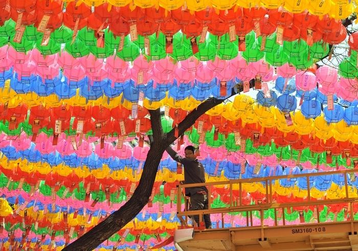 Een Zuid-Koreaan hecht naamkaartjes met gelukswensen aan lantaarnen in een boeddhistische tempel in Seoul.