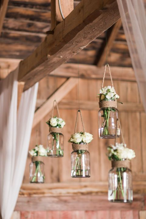 This rustic barn wedding nails county decor! We're loving how the decor included Mason jar flower holders and repurposed suitcases.