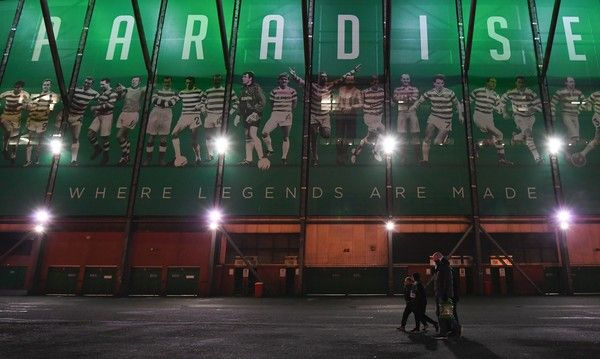 People walk by a large picture on the side of Celtic Park in Glasgow on November 23, 2016 ahead of the UEFA Champions League group C football match between Celtic and Barcelona.  / AFP / Paul ELLIS