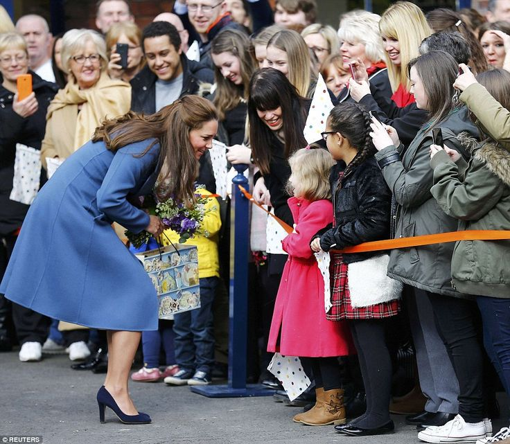 Hello there: The Duchess, 33, crouched down to chat with a little girl in a pretty pink co...