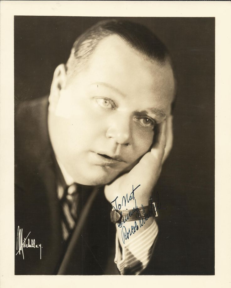 ARBUCKLE ROSCOE 'FATTY': (1887-1933) American Silent Film Comedian. Rare signed and inscribed sepia 8 x 10 photograph of Arbuckle in a head and shoulders pose resting his head in one hand. Photograph by Mitchell of New York. Signed in dark fountain pen ink to the image, 'To Nat, Sincerely, Roscoe Arbuckle', his surname partially running across a darker area.