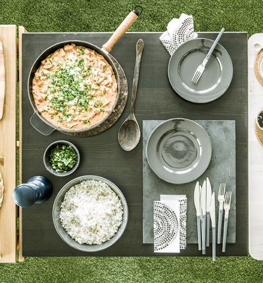 Pohľad zhora na prestretý stôl s panvicou s párkovým stroganovom a miskou ryže