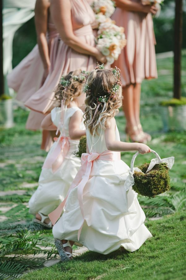 Love the dresses with pink sashes and the earthy moss baskets!