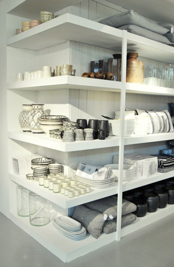 white shelves turn a corner, the items are displayed in an open way they look sculptural and quite lovely. Organized in groups