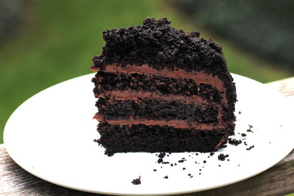 """The visual of this cake, with its shaggy coating of dark cake crumbs, harkens back to the Ebinger's Blackout Cake beloved in the New York area. The bakery closed its doors in the early 1970s and the original blackout cake recipe was never published; our version uses """"black"""" cocoa, which has the color and flavor of an Oreo cookie."""