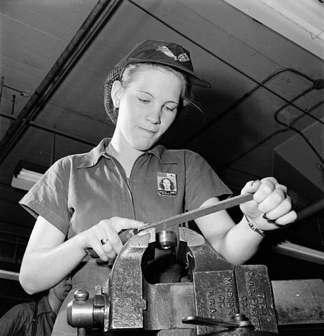 Woman factory worker files a machine part while piped music plays on loudspeakers. Montreal, Quebec, Canada. November 1943.