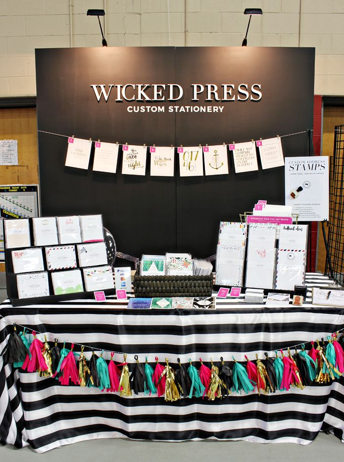 DIY Craft Fair booth featuring risers made out of black foam core, a tissue tassel garland in gold, black, pink and turquoise, and a black and white striped table cloth. By Wicked Press/Wicked Bride