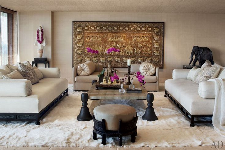 A 19th-century Indian tapestry with gold and silver thread offers a dramatic backdrop for the master suite in the Los Angeles duplex of Cher. Designer Martyn Lawrence-Bullard created the sofas and the low table. The Tibetan monk statue is 18th century; the carved elephant is early 19th century.
