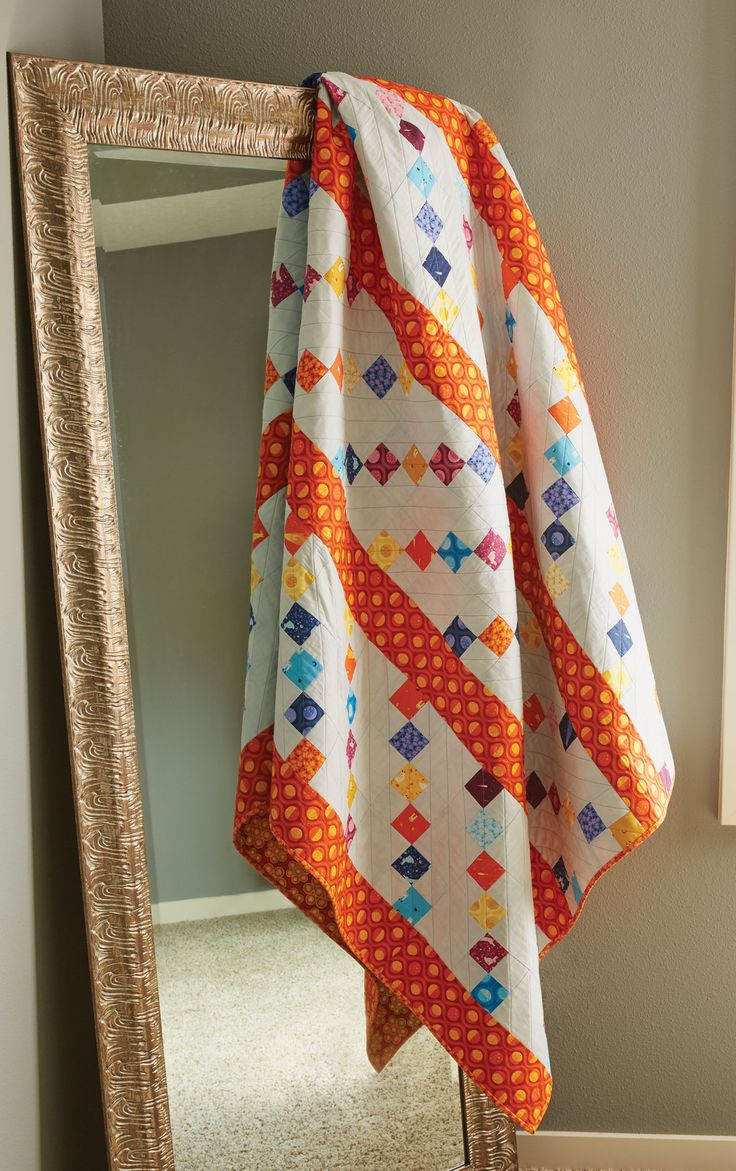 Vivid hues inspired by burning sunrises and calming sunsets make this quilt a favorite among quilters who love color. Orange sashing offsets simple but colorful four-patch units in this bed-sized quilt pattern, making it come to life when assembled. We offer tips for perfect alignment of rows, too!