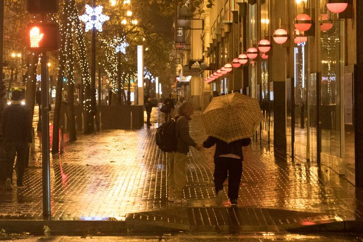 Pedestrians cover up during a light rainfall this morning in downtown San Francisco on Dec. 10, 2015.