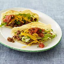 SPICY BEEF TACOS ~ 2 cloves garlic, minced ~ 3/4 pound(s) uncooked 93% lean ground beef ~ 1 1/2 tsp ground cumin ~ 1 1/2 tsp ground coriander ~ 3/4 tsp salt  ~ 1 1/2 cups canned diced tomatoes, with jalapenos or green chilies ~ 8 small corn tortilla, lightly toasted just before serving if desired* ~ 2 cup lettuce, shredded ~ 1/2 cup low-fat shredded Cheddar cheese, sharp-variety ~ 1/3 cup fat free salsa